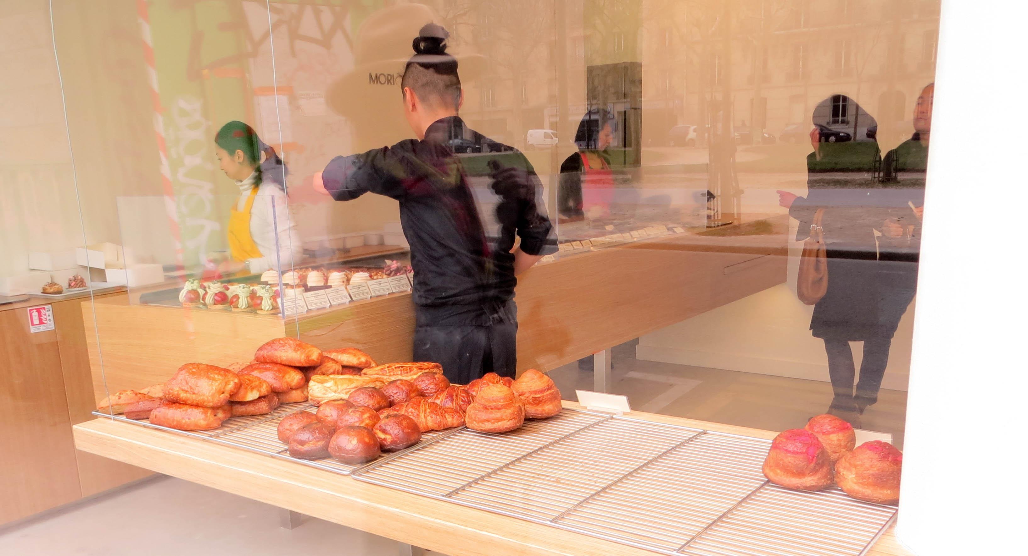 Morihide Yoshida de dos dans sa boutique, avec au premier plan les  viennoiseries présentées sur