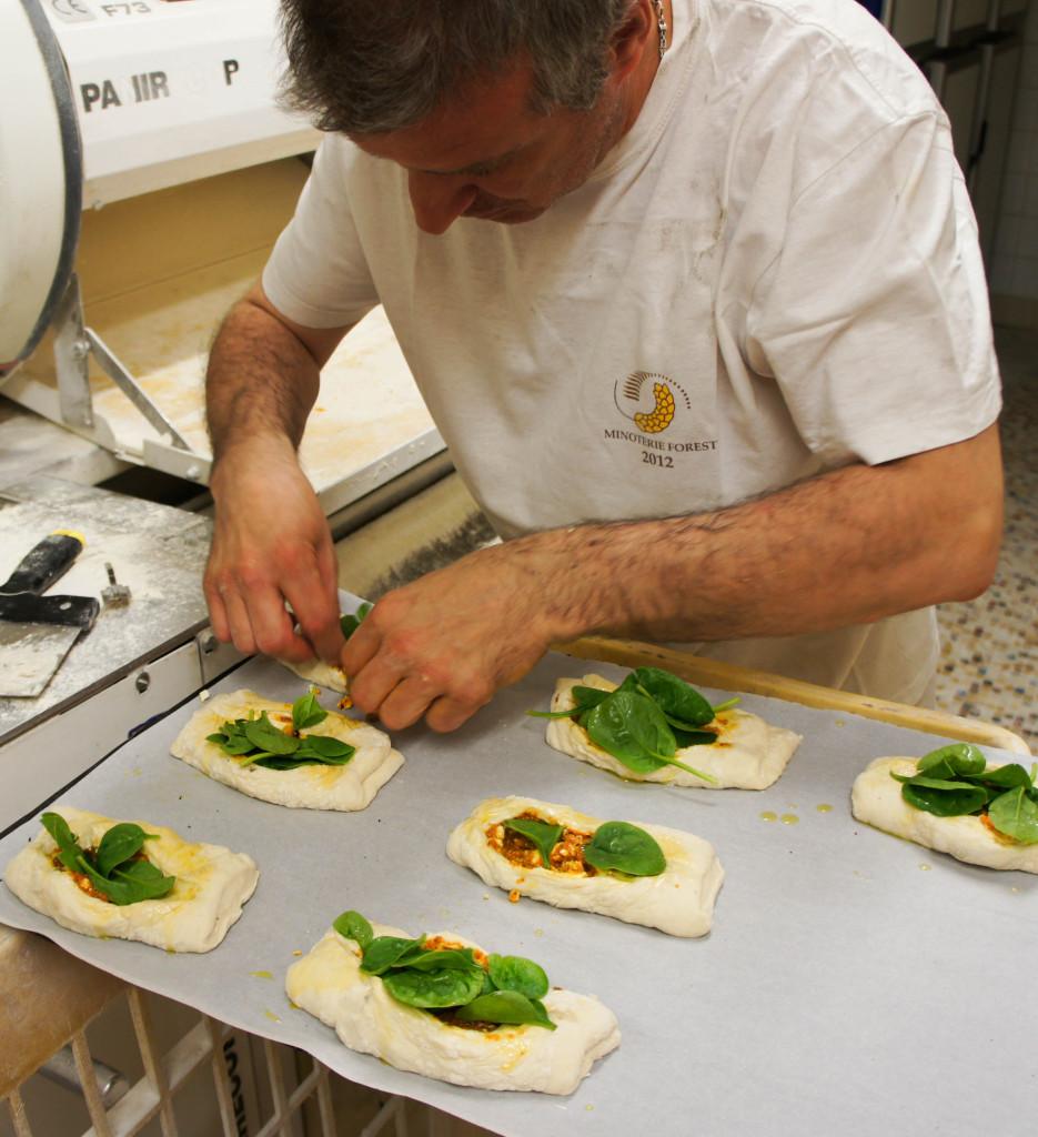 Au sous-sol, Didier Marchand confectionne avec beaucoup de soin les petits pains gourmands, garnis de leurs mélanges de légumes et fromages.