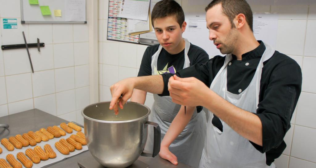 La fin d'année scolaire est une période propice aux stages. Ici, Arnaud, le responsable de production, explique à un jeune comment gratter efficacement une gousse de Vanille. Une tâche anodine, mais faisant partie du quotidien d'un pâtissier.