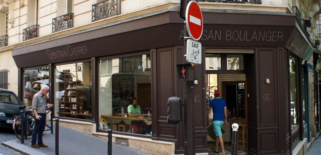 En descendant la rue Caulaincourt vers la place de Clichy, la belle boulangerie d'angle de Gontran Cherrier attire l'oeil par ses larges baies vitrées et son aménagement sobre. Cette boutique tout en longueur offre aux clients la possibilité de consommer sur place, grâce à des tables-mange debout disposés face aux vitrines extérieures. Autant lieu de vie que de passage, cette boulangerie contemporaine ne manque pas de charme, de simplicité et d'élégance.