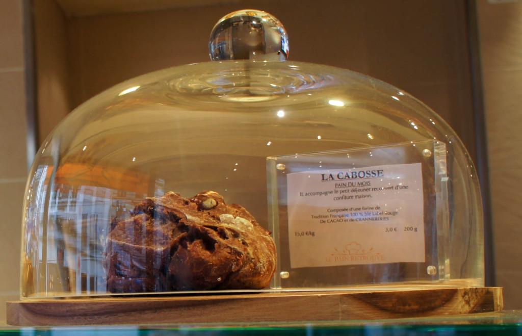 Le pain du mois, La Cabosse, au cacao et cranberries, présenté sous cloche.