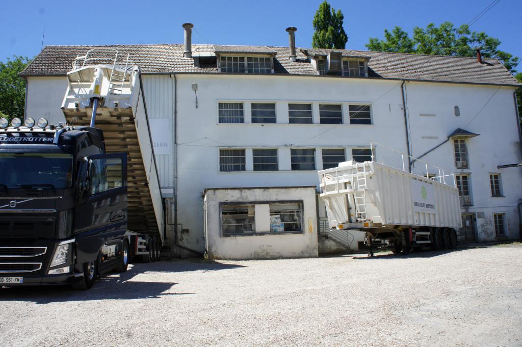 A gauche, le camion décharge le grain. La remorque à gauche stocke du son qui sera ensuite valorisé. Au milieu, derrière les fenêtres, les meules et cylindres s'activent.