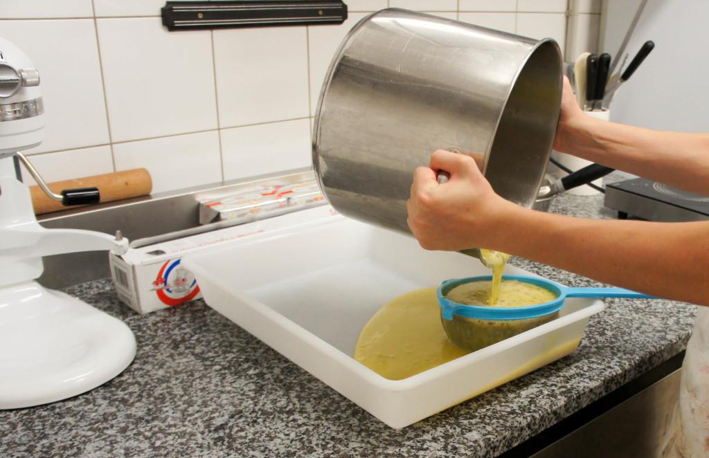 L'apprenti pâtissier est en train de passer la crème citron-basilic de la dernière création pâtissière proposée en boutique. Une association fraiche et agréable, parfaite pour un goûter d'été.