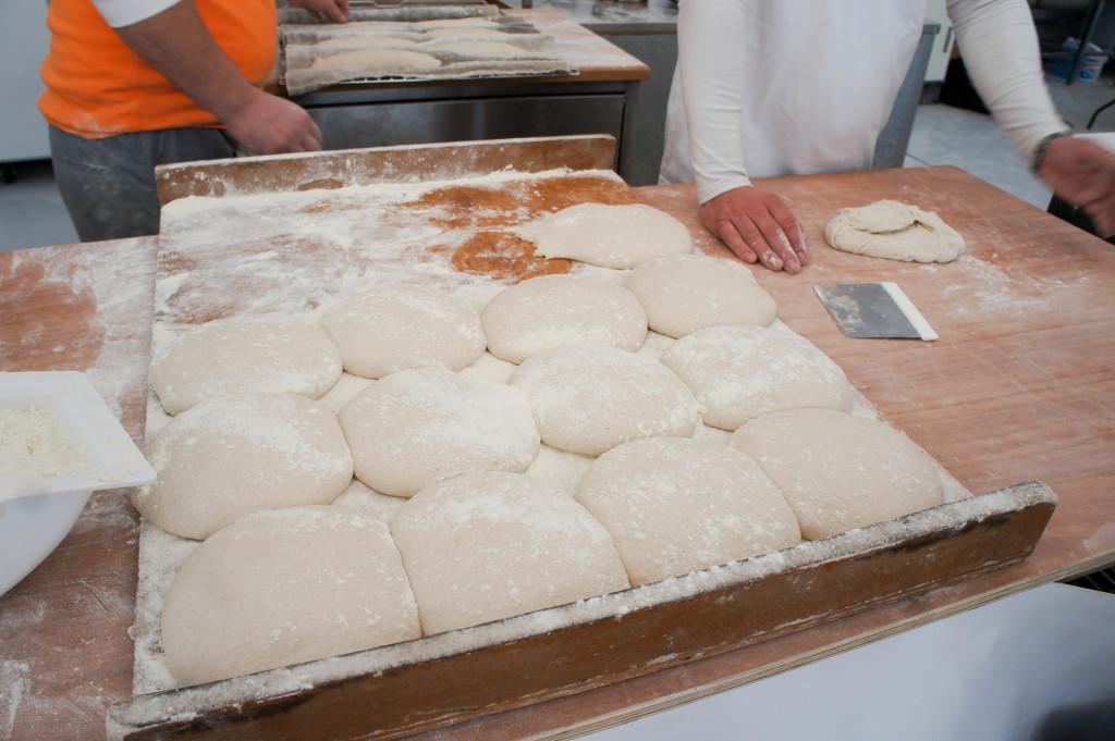 Des pâtes et des mains... le travail du façonnage suit son cours au fournil.