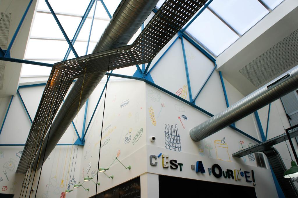 La grande verrière arrose l'ensemble du bâtiment en lumière naturelle. Sur les murs, les mots et illustrations renforcent l'univers.