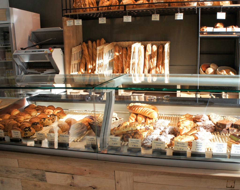 La boutique est naturellement baignée par la lumière, grâce à son emplacement d'angle et ses larges baies vitrées. Ainsi, les pains et viennoiseries se trouvent teintés d'or...