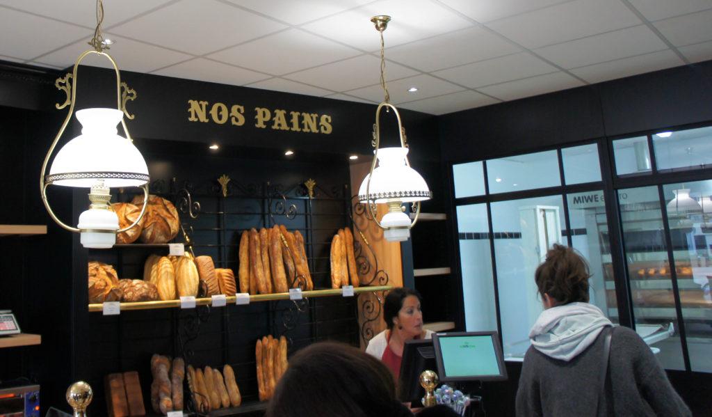Le mur à pain est situé à proximité immédiate du fournil, visible entièrement au fond de la boutique.