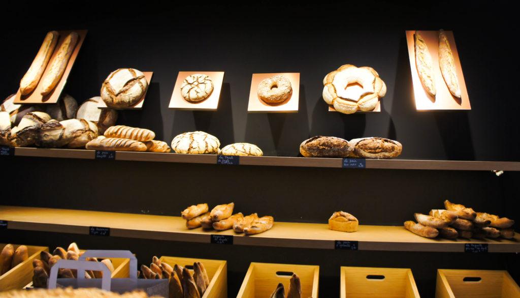 """Le mur à pains revêt une dimension très théâtrale... Un peu trop ? La gamme demeure assez classique : tourtes de Meule et de Seigle, pain de Seigle ou d'épeautre, pain aux noix, Tradition, baguette """"Loyale"""" (farine bio et pointe de Seigle). Cuissons bien menées et belles croûtes. Les farines sont livrées par les Moulins de Chars (et de Brasseuil pour le Bio / Label Rouge), partenaire de longue date de Thierry Marx au sein de son école."""